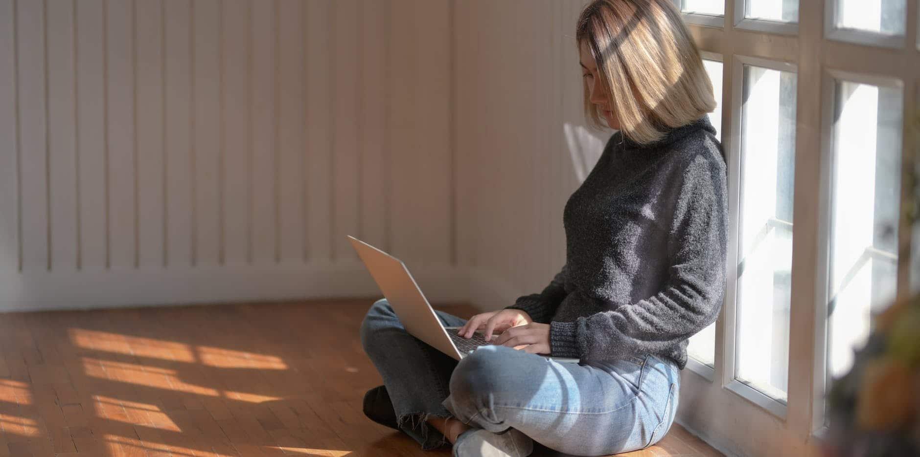 woman in gray sweater using laptop beside glass window